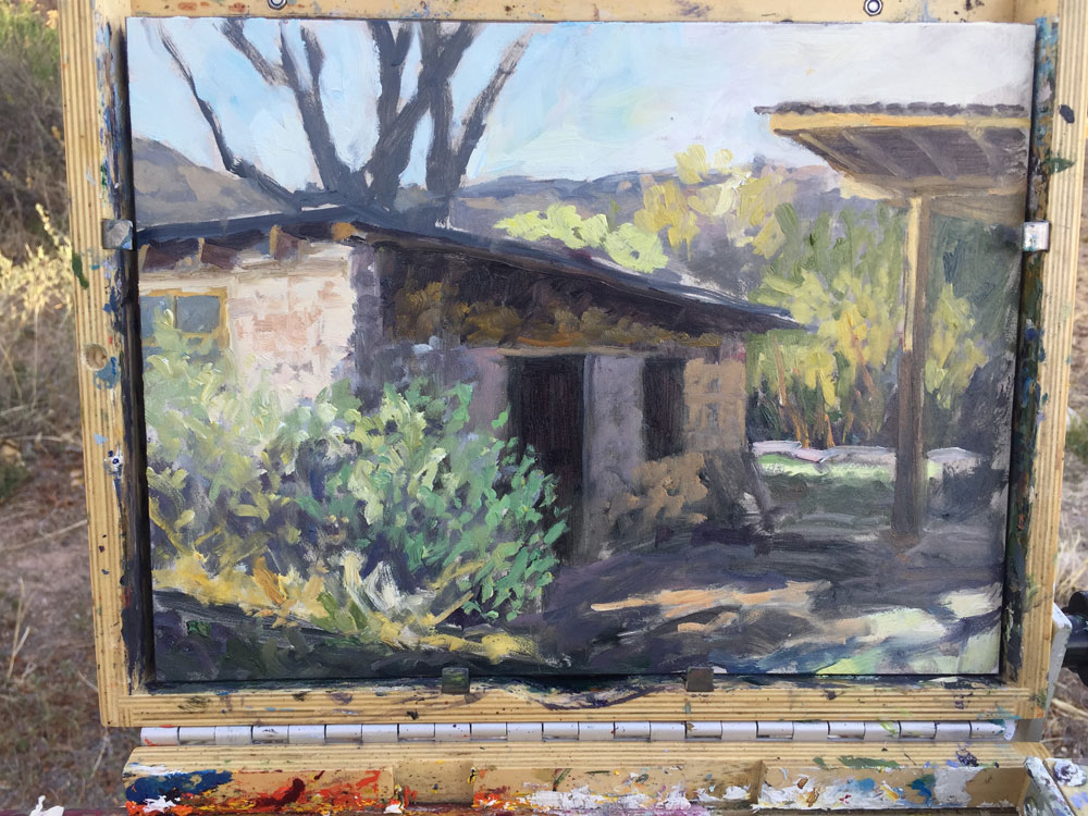 Dawn Chandler's laying in the color on a plein in painting of an adobe pottery shed in Dixon, New Mexico