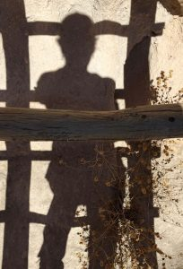 artist Dawn Chandler's shadowed silhouette against the canyon wall at Bandelier