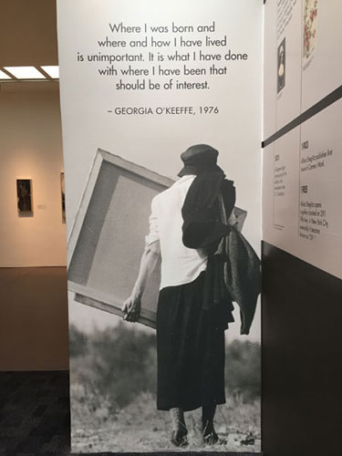 Museum exhibit banner of Georgia Okeeffe carrying a canvas outside