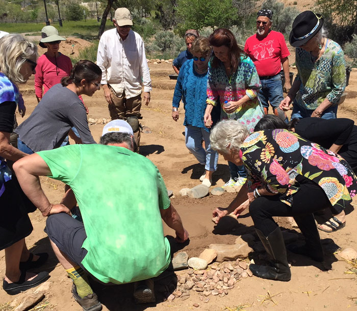 Neighbors gather stones to place around the earthen heart at the Frenchy's Park labyrinth in Santa Fe. Photo by Dawn Chandler.