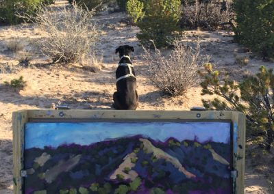 Artist Dawn Chandler being guarded while painting en plein air outside of Santa Fe