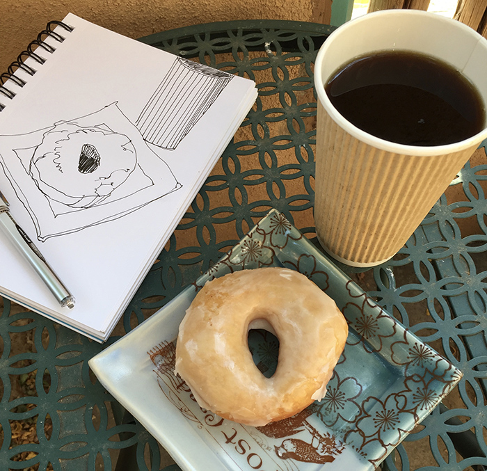 Sketchbook, coffee and a glazed donut.