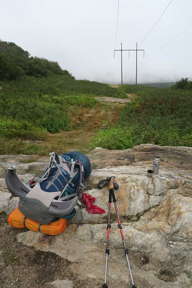 Pack and power-lines under a grey sky on the Long Trail, Vermont. Photo by Dawn Chandler.